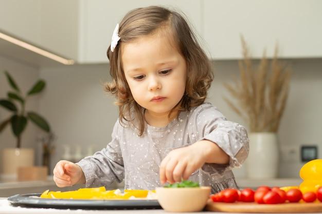 Menina bonitinha 2-4 no vestido cinza, cozinhar pizza na cozinha. kid arruma ingredientes em uma base de pizza