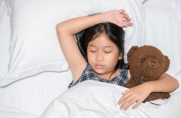 Menina bonitinha abraçando o ursinho de pelúcia dormindo deitada na cama, criança feliz abraçando o brinquedo adormecer em lençóis brancos de travesseiro macio coberto com cobertor, vista de cima