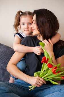 Menina bonitinha abraçando sua linda mãe