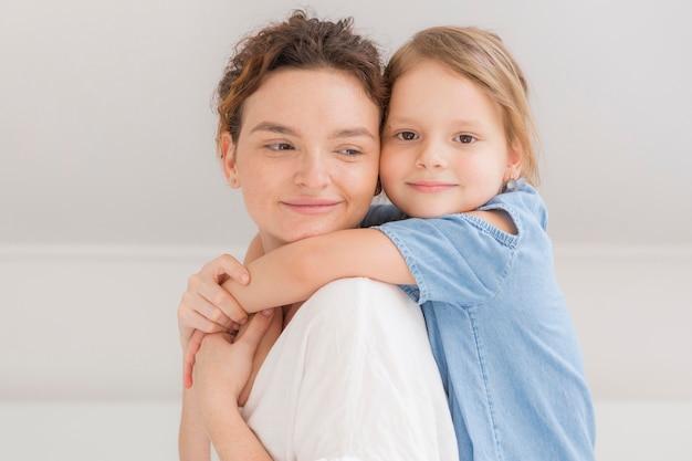 Menina bonitinha abraçando sua mãe