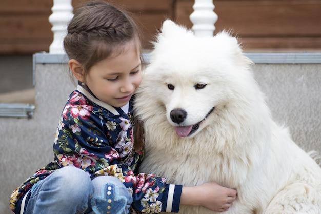 Menina bonitinha abraçando um cachorro branco no parque