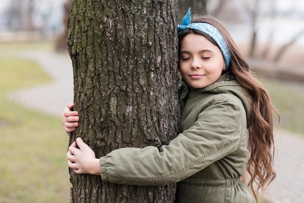 Menina bonitinha abraçando uma árvore