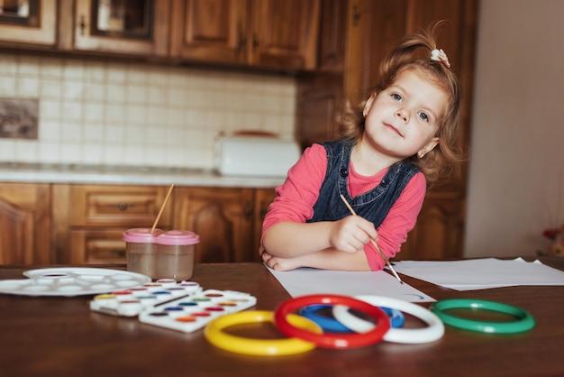 Menina bonitinha, adorável pré-escola pintura com aquarelas
