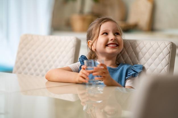 Menina bonitinha água potável na cozinha em casa. prevenção de desidratação