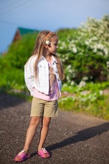 Menina bonitinha andando ao ar livre, se divertindo e rindo