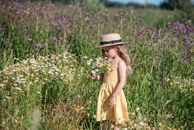 Menina bonitinha andando no campo de flores no vestido amarelo e chapéu, horário de verão