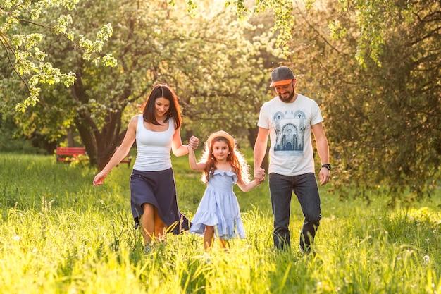 Menina bonitinha andando no parque segurando as mãos dos pais