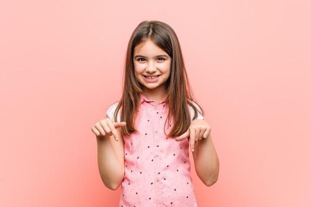 Menina bonitinha aponta para baixo com os dedos, sentimento positivo.