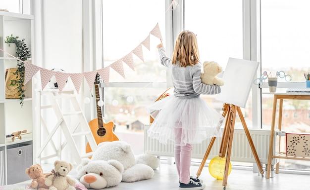 Menina bonitinha apontando para a janela de ursinho de pelúcia na sala de jogos