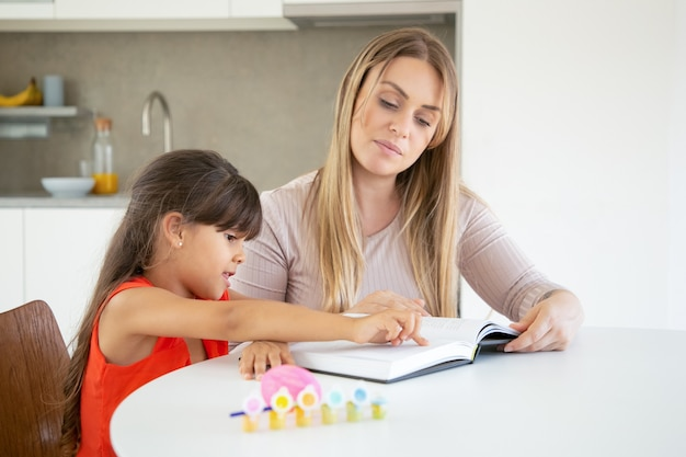 Menina bonitinha apontando para o texto e aprendendo com a mãe.