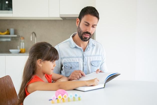 Menina bonitinha apontando para o texto e aprendendo com o pai.
