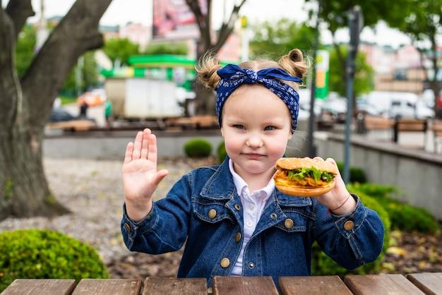 Menina bonitinha apontou gesto de parada com hambúrguer nas mãos antes de comer em um café ao ar livre
