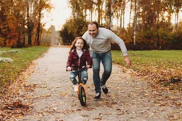 Menina bonitinha aprendendo a andar de bicicleta no parque ao ar livre com o pai.