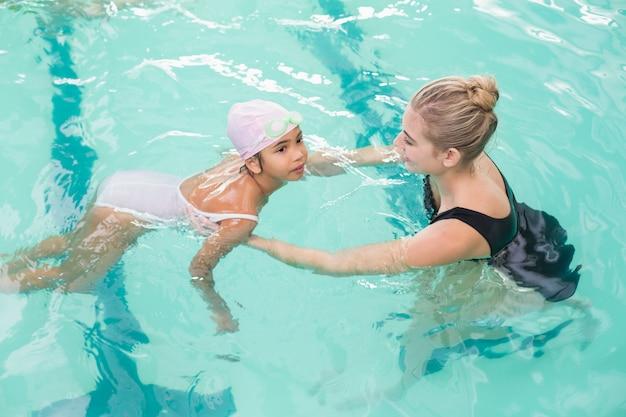 Menina bonitinha aprendendo a nadar com o treinador no centro de lazer