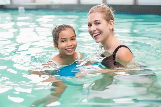 Menina bonitinha aprendendo a nadar com o treinador