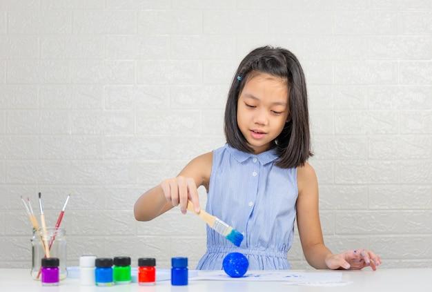 Menina bonitinha aprendendo sistema solar fazendo modelo com pintura em bola de espuma