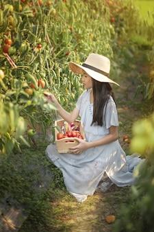 Menina bonitinha asiática com tomates vermelhos