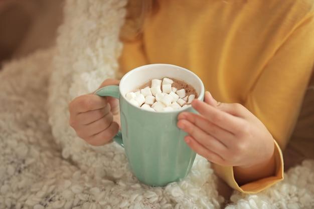 Menina bonitinha bebendo chocolate quente com marshmallow, closeup