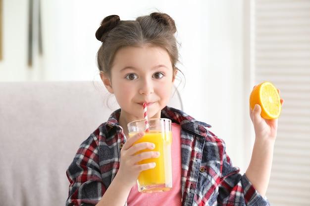 Menina bonitinha bebendo suco em casa
