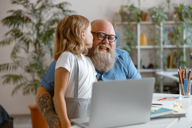 Menina bonitinha beijando papai sorrindo e agradecendo por ajuda com o dever de casa na sala iluminada