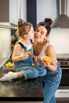 Menina bonitinha beijando sua linda mãe