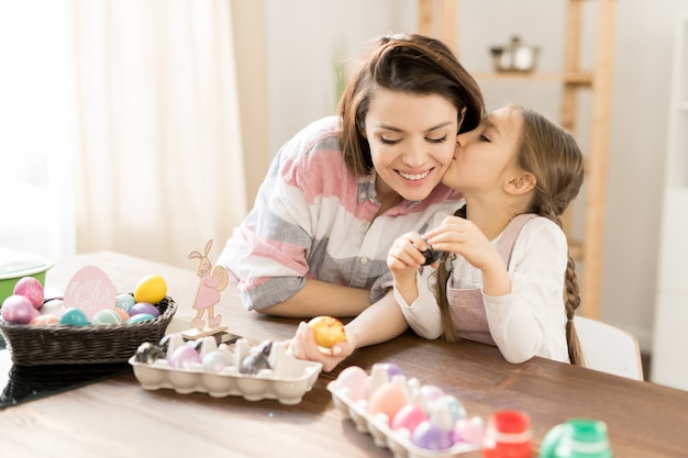 Menina bonitinha beijando sua mãe enquanto está sentado à mesa e selecionando os ovos de páscoa para dar a amigos e parentes