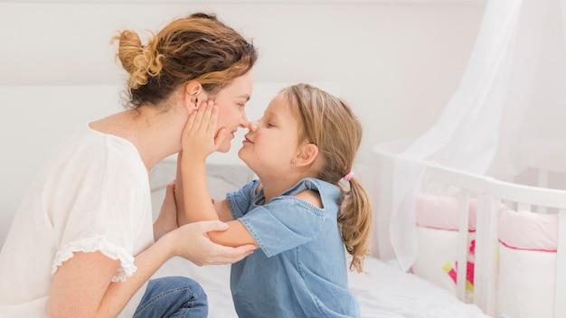 Menina bonitinha brincando com a mãe em casa