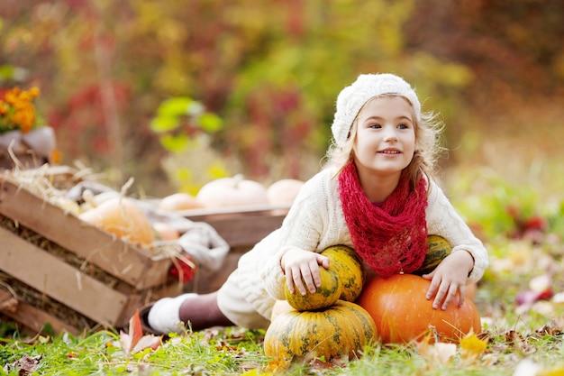 Menina bonitinha brincando com abóboras no parque outono. atividades de outono para crianças. dia das bruxas e diversão de tempo de ação de graças para a família.