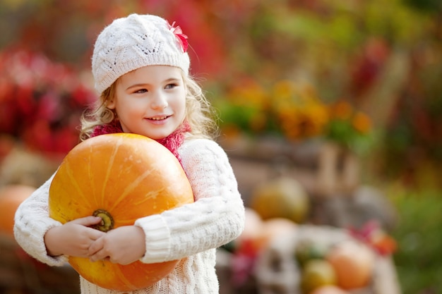 Menina bonitinha brincando com abóboras no parque outono. atividades de outono para crianças