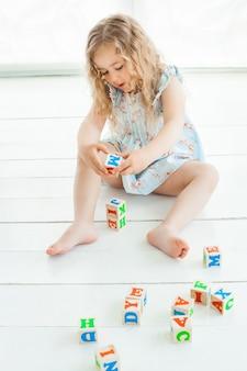 Menina bonitinha brincando com cubos abc dentro de casa