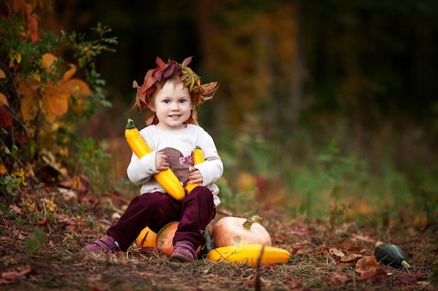 Menina bonitinha brincando com medula vegetal no outono park. atividades de outono para crianças. dia das bruxas e diversão de tempo de ação de graças para a família. copie o espaço