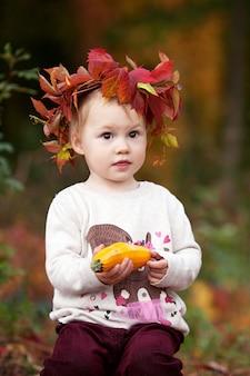 Menina bonitinha brincando com medula vegetal no outono park. atividades de outono para crianças. dia das bruxas e diversão de tempo de ação de graças para a família.