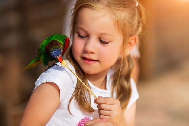 Menina bonitinha brincando com um papagaio e alimentá-lo
