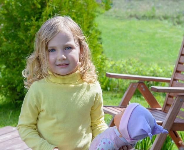 Menina bonitinha brincando com uma boneca no jardim.