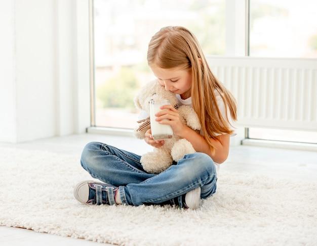 Menina bonitinha brincando com ursinho de pelúcia