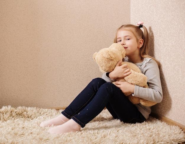 Menina bonitinha brincando com urso