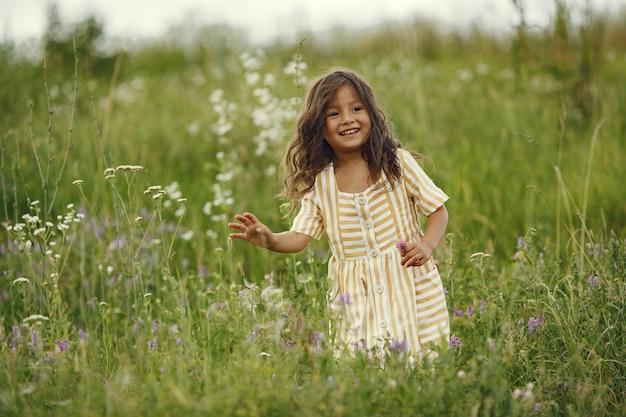 Menina bonitinha brincando em um campo de verão