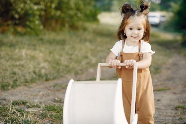 Menina bonitinha brincando em um parque com carruagem branca