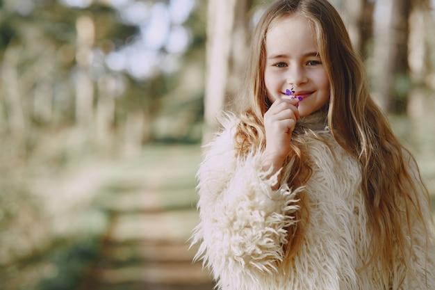 Menina bonitinha brincando em uma floresta de verão