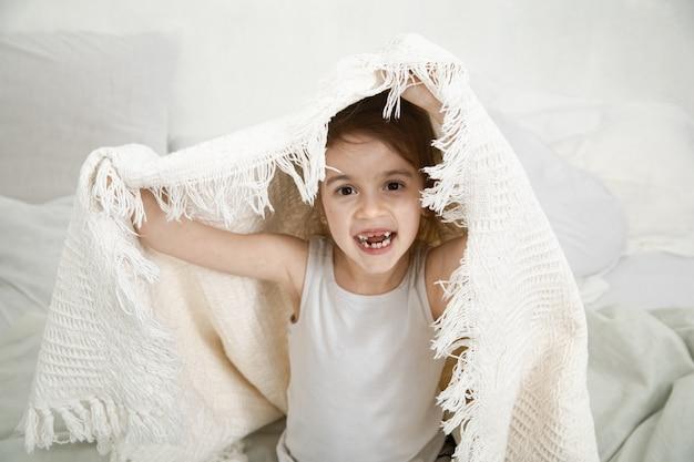 Menina bonitinha brincando na cama com um cobertor.