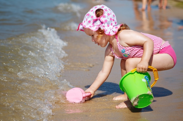 Menina bonitinha brincando na praia