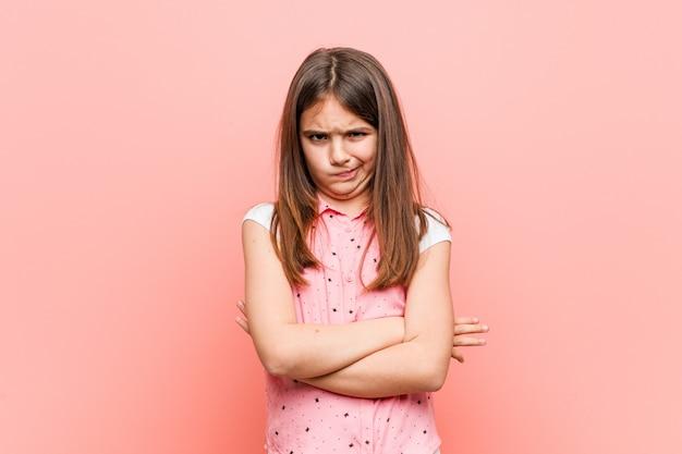 Menina bonitinha carrancuda rosto em descontentamento, mantém os braços cruzados.