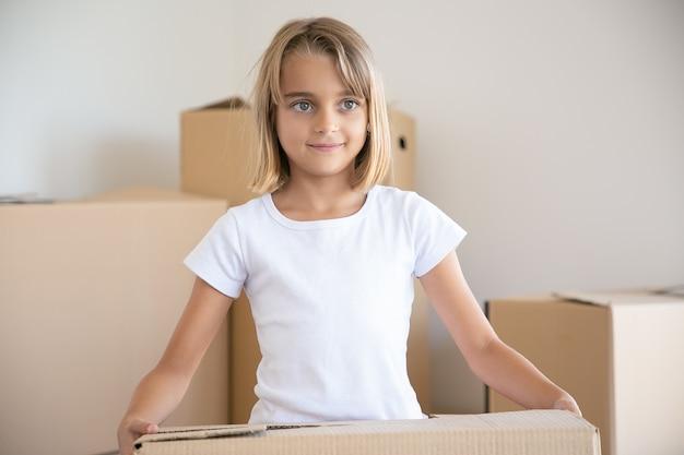 Menina bonitinha carregando caixa de papelão e olhando para longe
