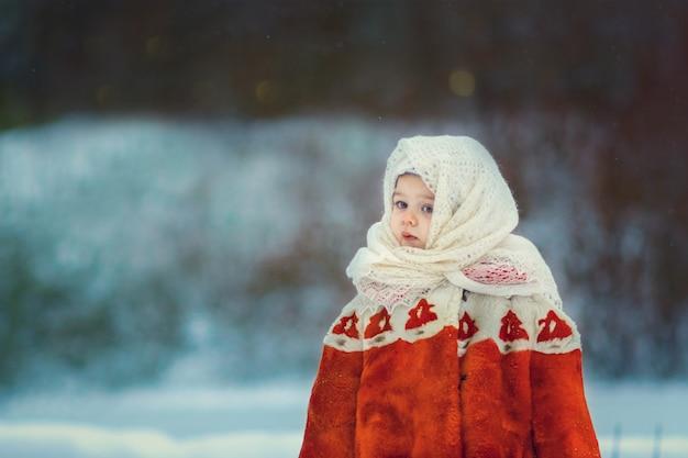 Menina bonitinha caucasiana com casaco de pele de imitação soviética retrô e xale de lã