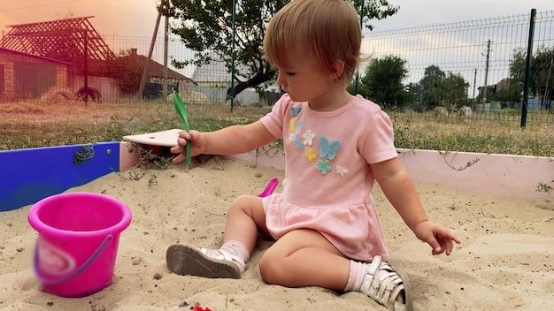 Menina bonitinha caucasiana com vestido rosa brinca na caixa de areia com pá e balde ao ar livre no verão em 4k