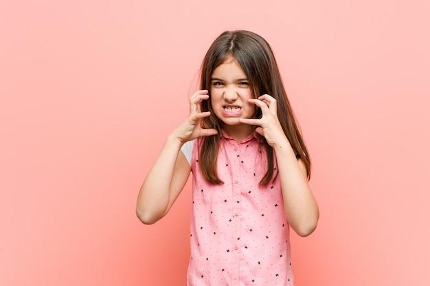 Menina bonitinha chateado gritando com mãos tensas.