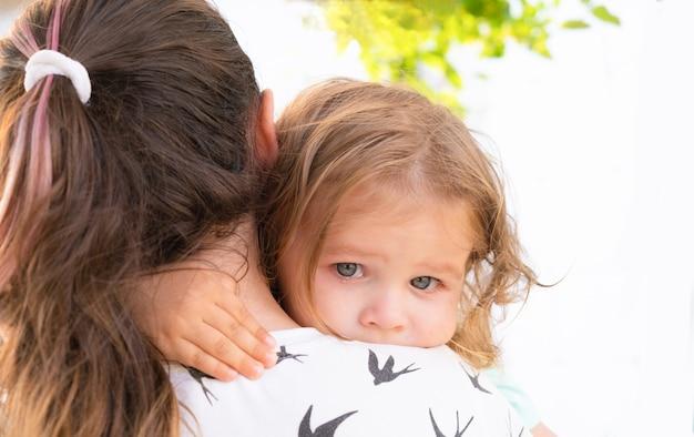 Menina bonitinha chorando e abraçando a mãe
