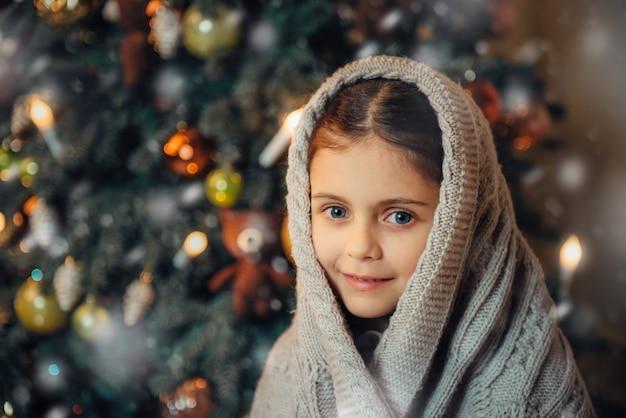 Menina bonitinha coberta de cachecol quente à espera de natal