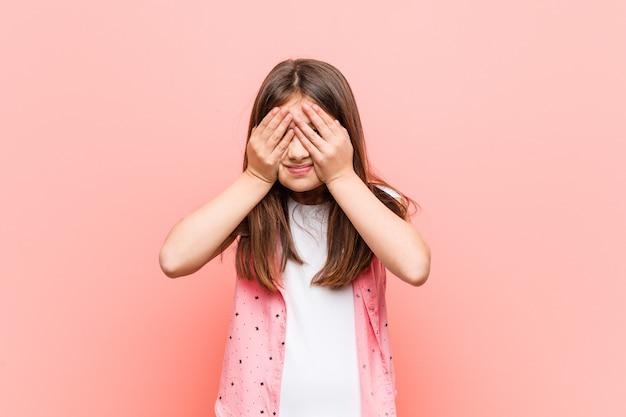 Menina bonitinha cobre os olhos com as mãos, sorri amplamente esperando por uma surpresa.