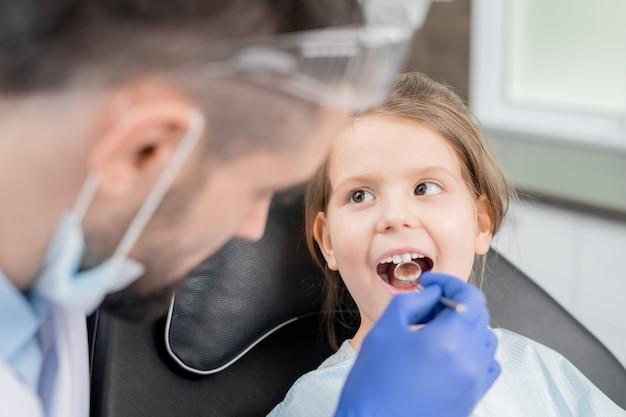 Menina bonitinha com a boca aberta, olhando para o dentista com luvas, curvando-se sobre ela durante o check-up oral com espelho em clínicas dentárias